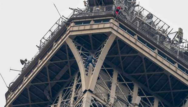 A man (C) climbs up the Eiffel Tower, in Paris, without any protection as a firefighter (R) looks do
