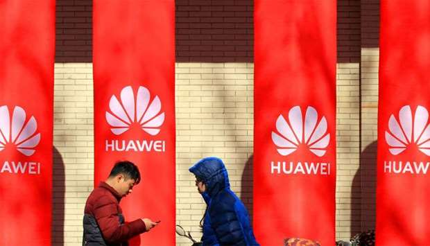 People walk past logos of Huawei