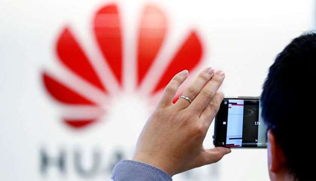 A man takes a picture of a Huawei logo