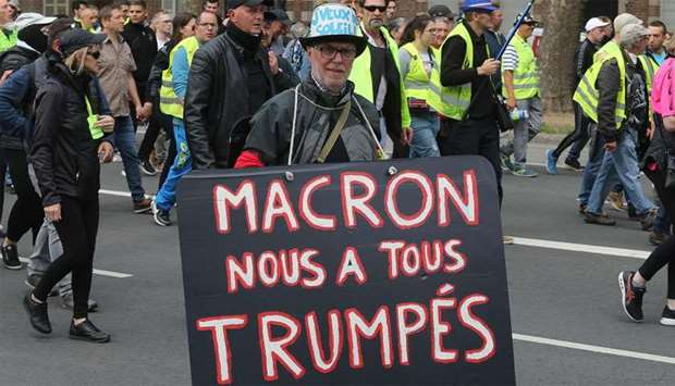 "A protester holds a sign reading ""Macron fooled us"" (A play on word on US President's name) during a"