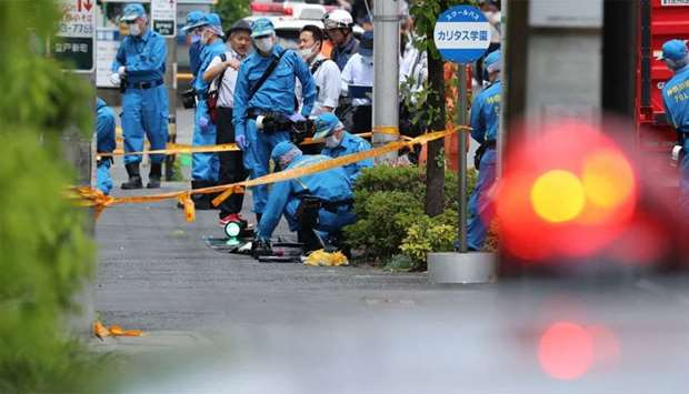 Police forensic experts investigate a crime scene where a man stabbed 19 people, including children