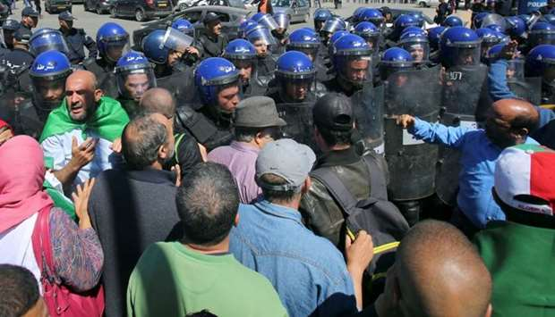 Police officers prevent demonstrators from marching during a May Day protest on Labour Day in Algier