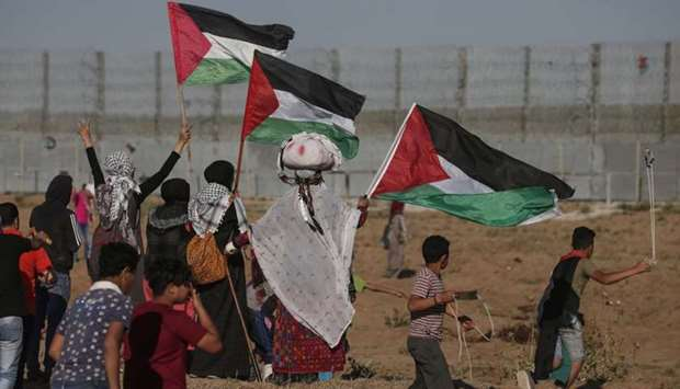 Palestinian protesters wave national flags during a demonstration along the border fence with Israel