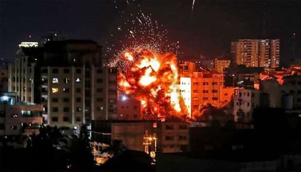 An explosion is pictured among buildings during an Israeli airstike on Gaza City