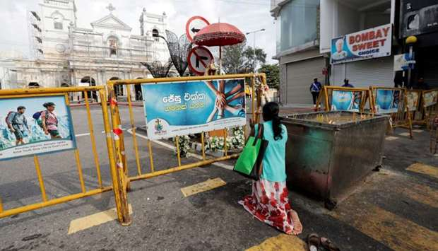 A Sri Lankan Catholic prays on the road in front of St. Anthony's Shrine, where an explosion took pl