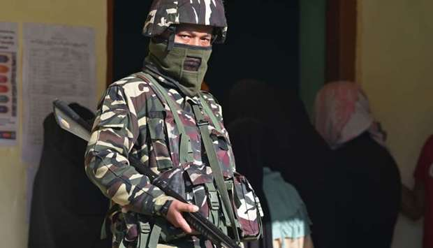 An Indian paramilitary trooper stands guard at a polling station during the third phase of India's g