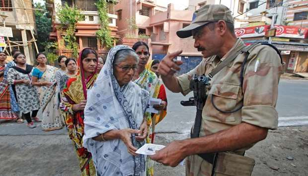 A security personnel checks the identity card of a woman as she stands in a queue with others to cas