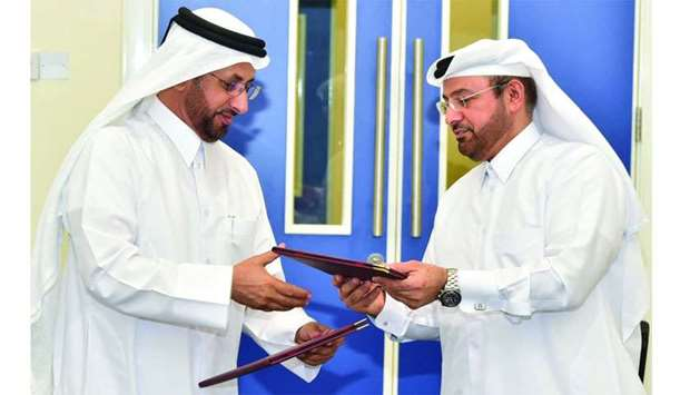 Prof Hamad al-Saad al-Kuwari and Dr Mohamad Yacoub al-Sulaiti exchange papers after signing an agree