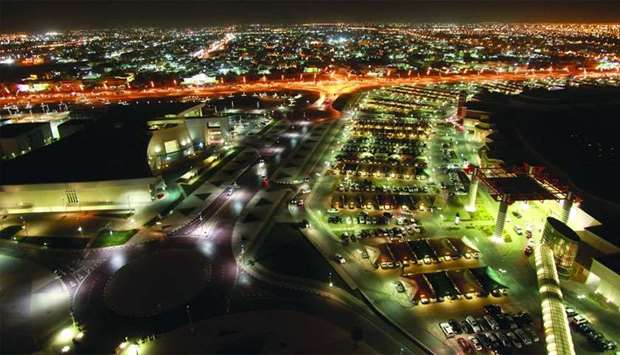 Buildings are seen illuminated at night in Doha. On a month-on-month basis, total number of permits