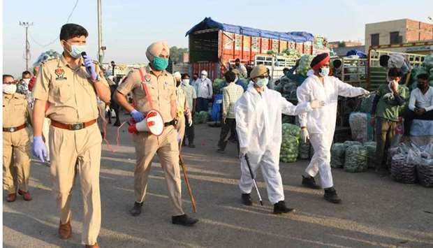 Punjab police personnel patrol at a vegetable wholesale market during a government-imposed nationwid