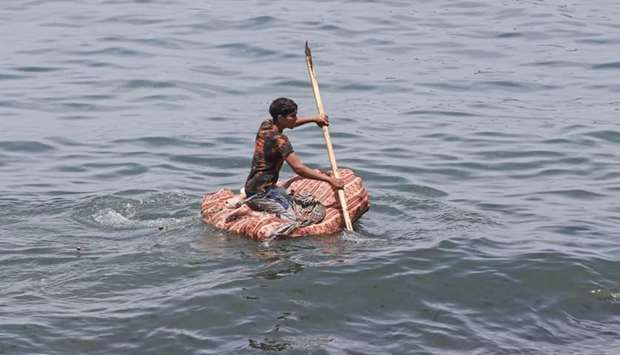 A Palestinian youth uses a float made of plastic bottles and fabric as he goes fishing on a hot day