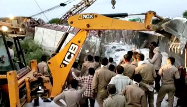 A police rescue team work to lift a truck afterat the site of an accident where a truck carrying mig