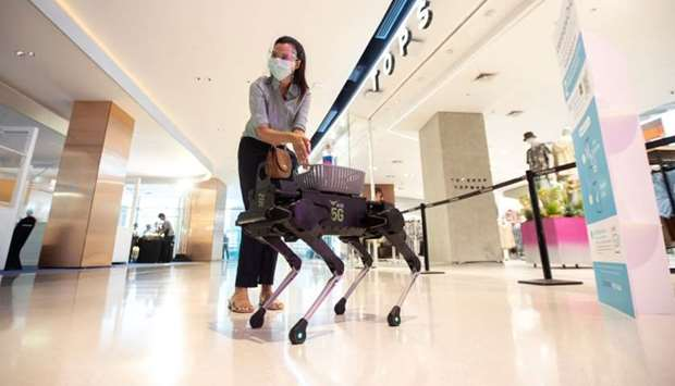A woman uses a sanitising hand gel from a four-legged dog robot called 'K9' at the Central World dep