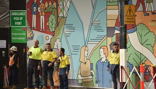 Construction workers take a break on a street in Sydney after more than seven weeks Covid-19 restric