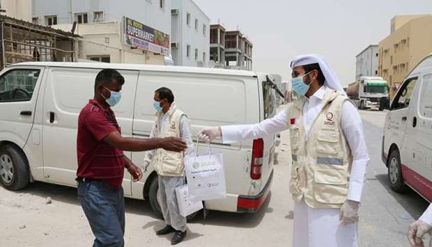 QFC, Qatar Charity volunteers distribute protective kits to Industrial Area workers.