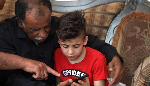 Hussein Dawabsha (left) sits with his grandson Ahmed, the survivor of the arson attack that killed h