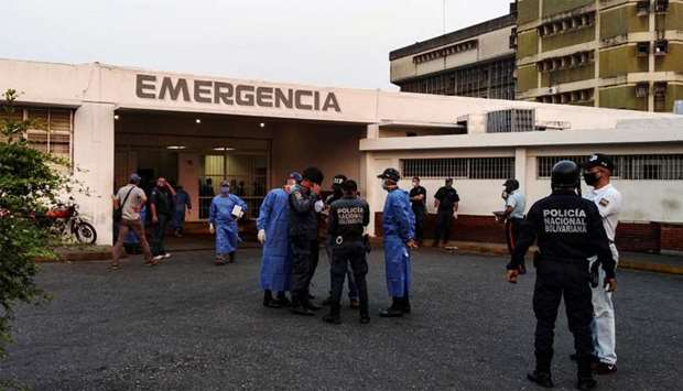 Healthcare workers and members of the Bolivarian national police wait for the arrival of prisoners o