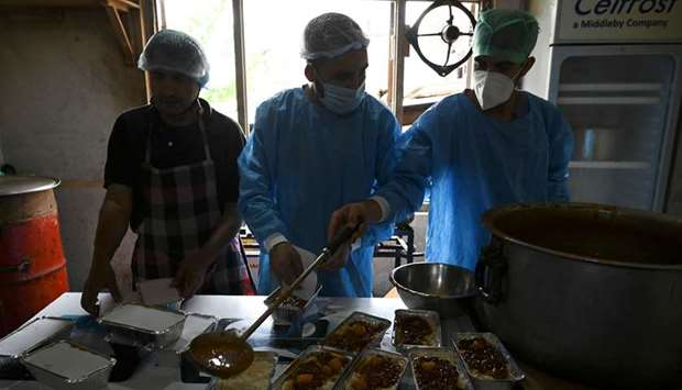 Workers pack food to be distributed in quarantine centres during a government-imposed nationwide loc