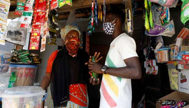 Shobowale Kehinde, 28, an entertainer who is visually impaired, buys a soft-drink bottle at a store