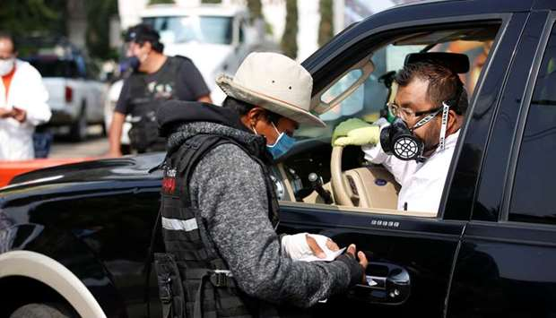 An employee of the municipality of Iztapalapa talks to the driver of a hearse, waiting to enter the