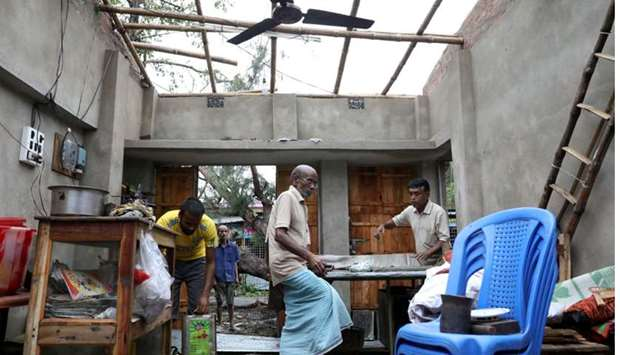 Men salvage items from a damaged shop after Cyclone Amphan made its landfall, in South 24 Parganas d