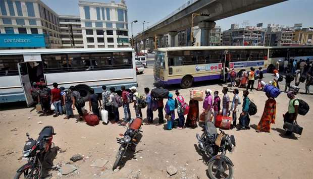 Migrant workers and their families get on buses to reach a railway station to board a train to their