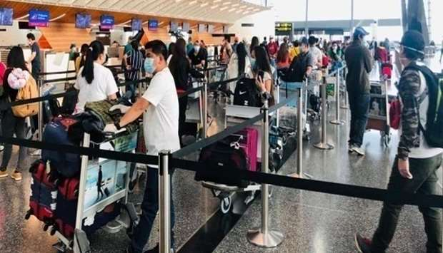 Filipino repatriates patiently queue up at the check-in counters of Hamad International Airport befo
