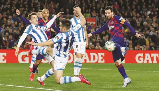 In this March 7, 2020, picture, Barcelona's Lionel Messi (right) shoots at goal during the La Liga m