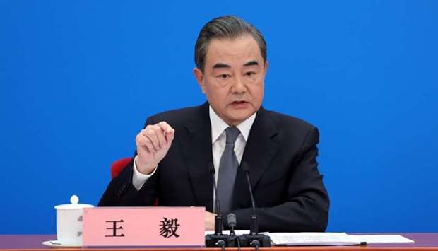 Chinese State Councillor and Foreign Minister Wang Yi speaks to reporters via video link at a news c