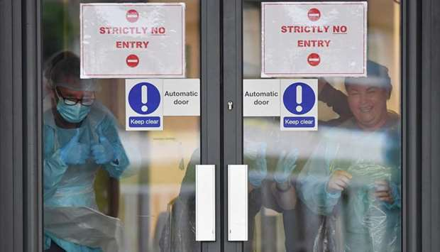 NHS staff in personal protective equipment (PPE) from behind a closed door gesture as they participa