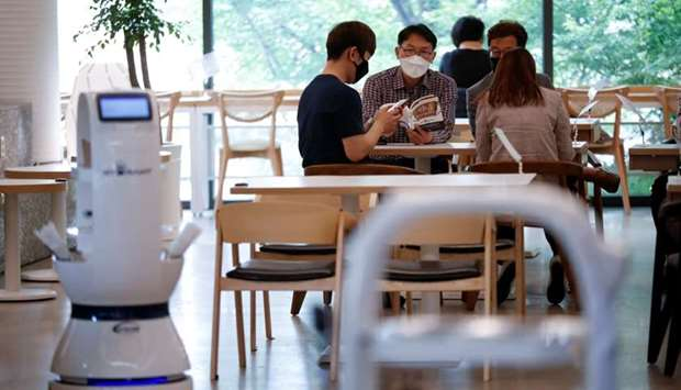 Customers wait at a cafe where a robot that takes orders, makes coffee and brings the drinks straigh