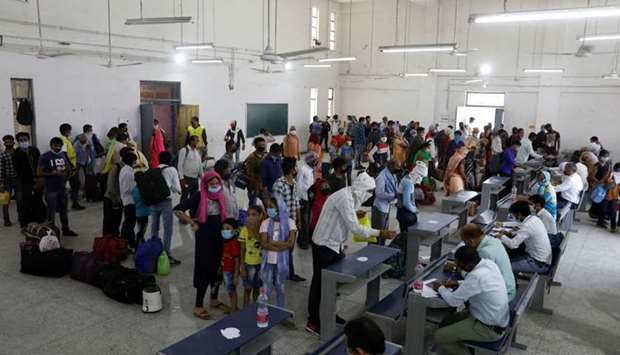 Migrant workers and their families stand in queues to get themselves registered for trains to their