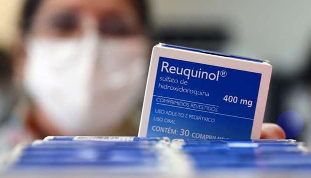 A health worker holds a box of hydroxychloroquine at the pharmacy of the Nossa Senhora da Conceicao
