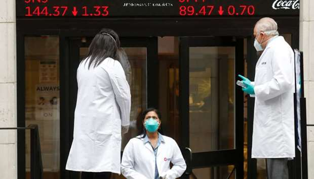 Medical personnel wear protective masks outside the New York Stock Exchange as the building opens fo