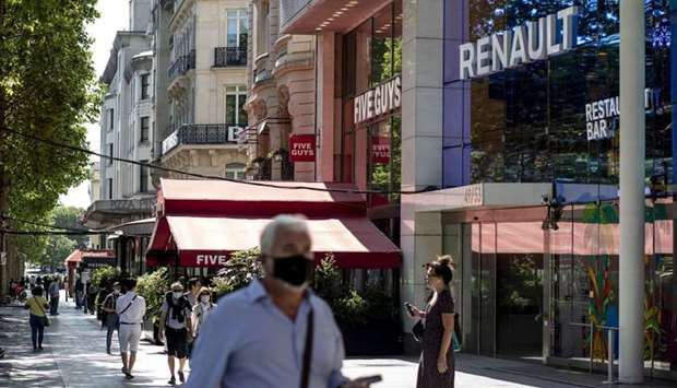 Pedestrians wear protective face masks outside the Renault flagship showroom on the Champs Elysee in