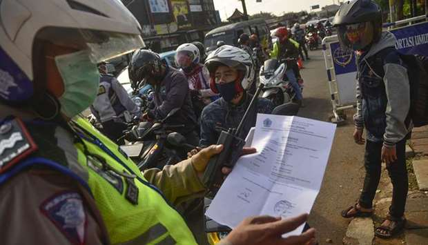 An Indonesian police officer inspects a document from a motorist heading toward the capital city of