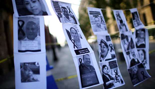 Photographs of healthcare workers who died from the coronavirus disease hang while health workers at