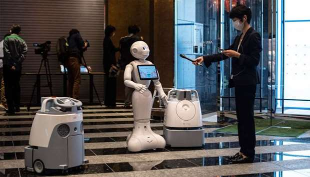 """A reporter (R) records the greeting voice of a robot called """"Pepper"""" (C) with two other cleaning rob"""