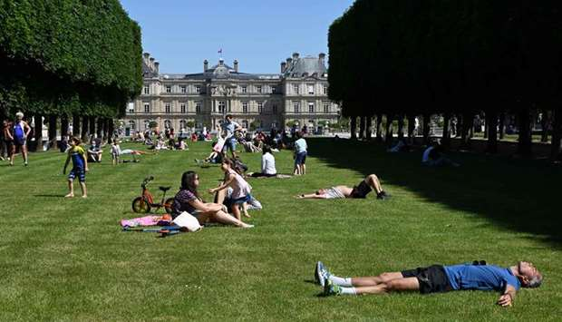 People lie and sit under the sun on the lawns of Paris's Jardin du Luxembourg park, on the first day