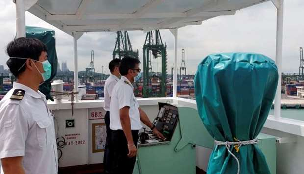 A crew member wearing a protective face mask sounds the horn of their boat, as all working ships sou