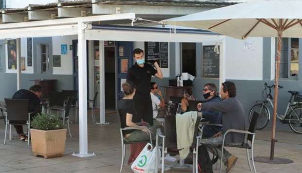 People are seen at an outdoors bar of the Balearic island of Formentera, Spain