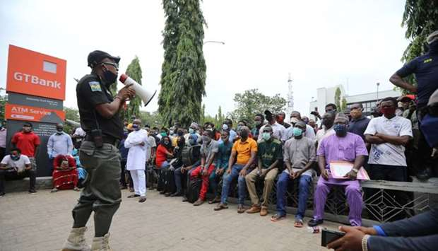 A police officer addresses the crowd at Guaranty Trust bank, as authorities ease the lockdown follow