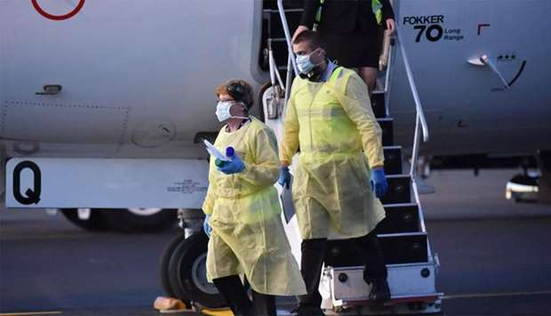 Australia biosecurity officials alight from a plane carrying the New Zealand Warriors rugby league t