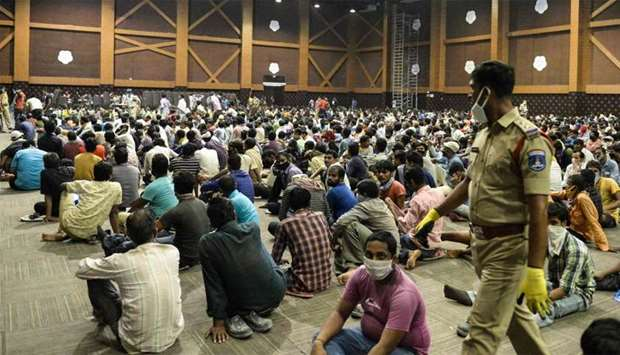 Stranded migrant workers sit in a waiting hall before registering with police officials for a moveme