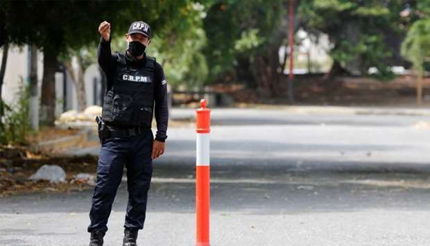 A member of the La Guaira state police gestures at a road checkpoint, after Venezuela's government a