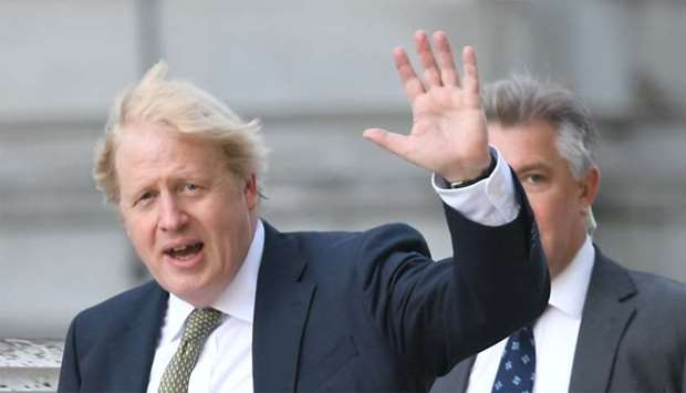 Britain's Prime Minister Boris Johnson waves as he takes a morning walk in central London