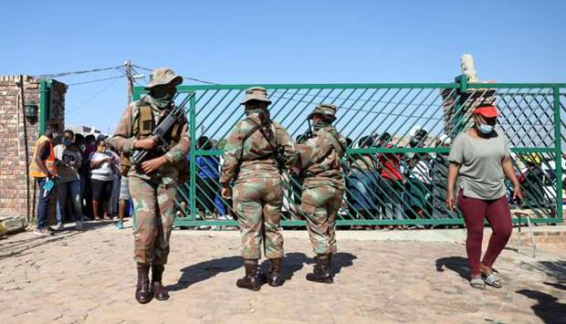 Military officers stand guard during food distribution, as South Africa starts to relax some aspects