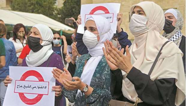 Women carry signs as they demonstrate to express solidarity with the Palestinian people near the Isr