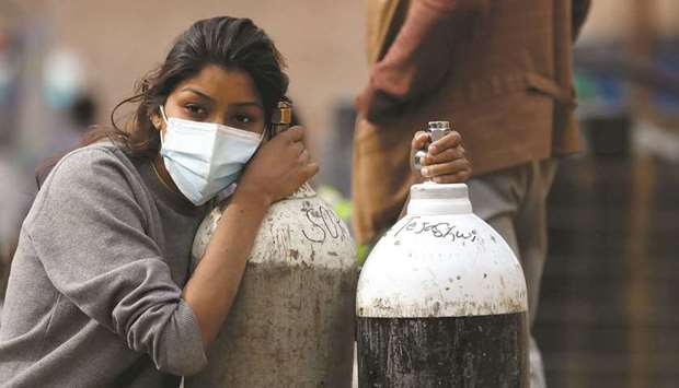 A woman holds on to the oxygen cylinders for a patient after re-filling them at a factory in Kathman