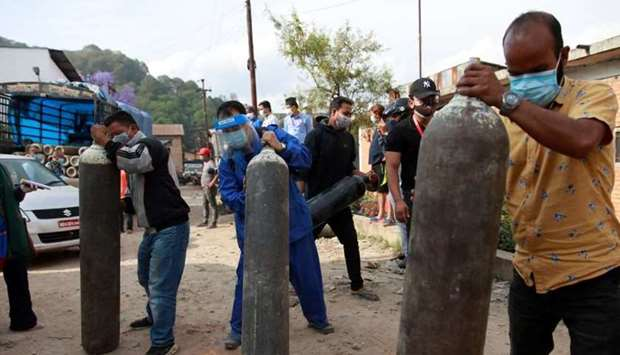 People carry oxygen cylinders for patients after refiling them at a factory in Kathmandu yesterday